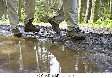 Hikers Walking Through Mud Puddle - Low section of hikers...