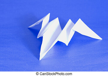 Plane - A paper airplane over a blue paper background