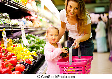 shopping in supermarket - mother and daughter shopping in...