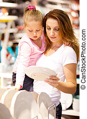 mother and daughter shopping in shop