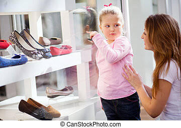 mother and daughter shopping, daughter pointing at shoes she...