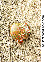 heart - A gemstone as heart on a wooden background