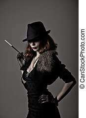 Retro shot of gangster woman in fedora hat and evening dress...