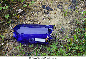 A broken Blue glass Bottle in the grass along side of a road...