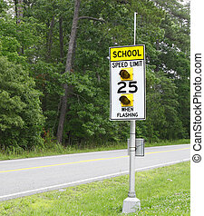 A School Speed limit sign with flashing lights along the...
