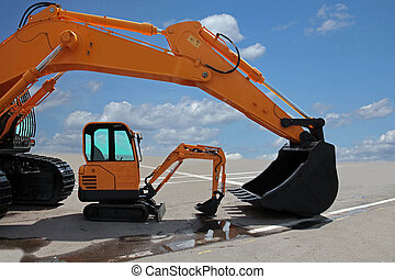 Two excavators on a concrete platform. Big and small...