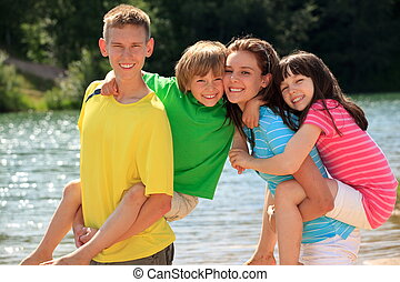 Happy children by lake - Group of four happy young brothers...