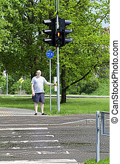 Man waiting for the green light to cross the pedestrian...