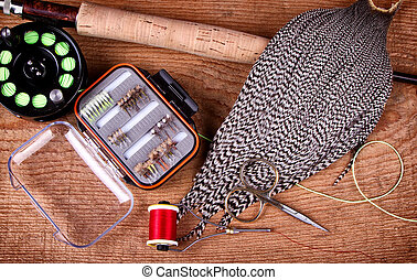 Collection of fly tying and fishing equiptment on a wooden...