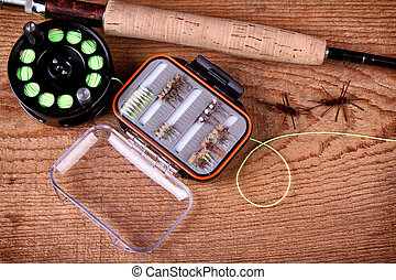 Collection of fly fishing equiptment on a wooden plank