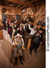 Customers in Old Saloon Toasting Drinks - Large group of...