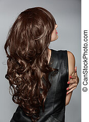 woman with long brown curly hair - back of the woman with...