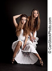 Two girls twins, isolated on the grey background - Two...
