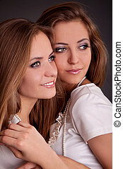 Two girls twins, isolated on the grey background - studio...