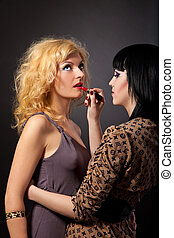 Two young attractive lesbians are hugging with a lipstick...