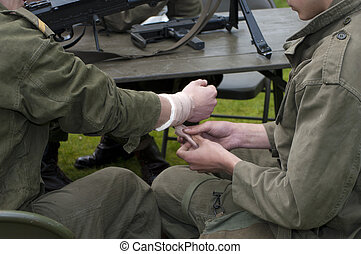 first aid - soldiers are demonstrating how to apply first...