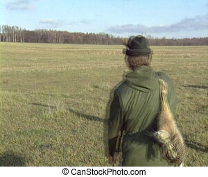 Hunter hare dog run side - Hunter with hunted hare on his...
