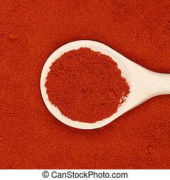 Paprika powder - A wooden spoon lies on paprika powder as...