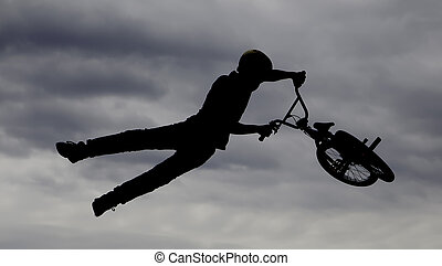 Airtime - Silhouette of BMX rider performing trick in mid...