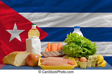 basic food groceries in front of cuba national flag