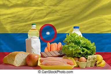 basic food groceries in front of colombia national flag