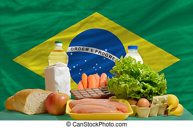 basic food groceries in front of brazil national flag -...