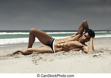 Hunk on beach - Fashion portrait of a sensual gorgeous male...