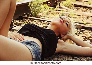 Beautiful young girl sleeping on rails Closeup - Beautiful...