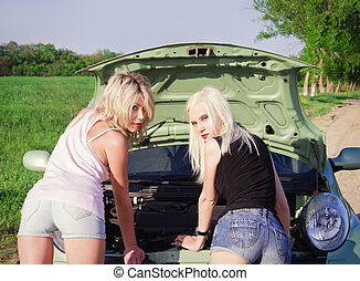 Two sexy blonde girls stand by the broken car. Rear view -...