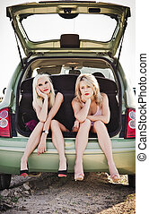 Two beautiful blonde girls sitting in trunk of broken car -...