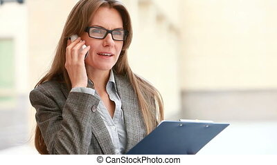 Doing business by phone - Ambitious business lady discussing...