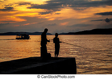 Silhouettes of father and his son fishing on sea -...