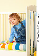 Kid in the bed - Small happy interested kid in the baby bed