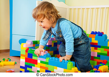 Happy kid climbing out of toy block in his room