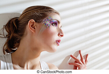 Woman standing by the window with blinds