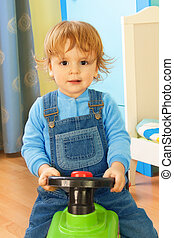 Portrait of a boy riding a toy car