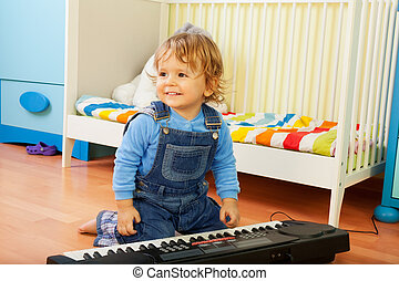 Boy playing a composer - Happy little boy playing a musical...