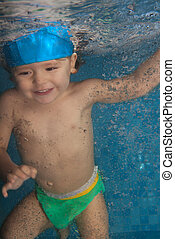 Happy toddler jumping in the pool