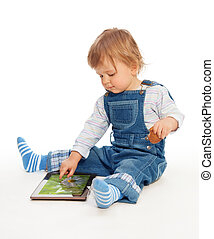 Young kid playing with tablet pc image on the screen from my...