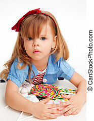 Greedy girl with pile of sweets laying on the table and with...