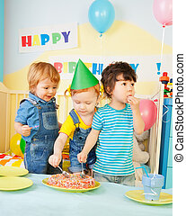 Three kids eating cake on the birthday party- two boys and...