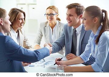 Deal - Partners concluding deal and shaking hands in the...