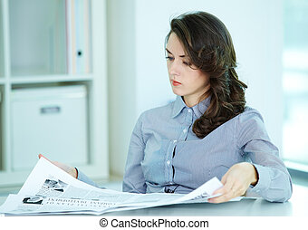 Fresh business news - Serious business woman looking through...