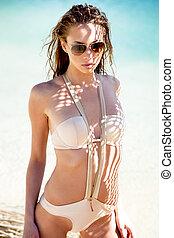 Bikini - Young woman on a beach in bikini and sunglasses