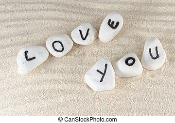 Love you words on group of stones with sand as background