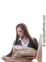 businesswoman - woman wraped up in brown paper trying to get...