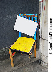 A Broken chair - Empty sign hanging on Old broken chair