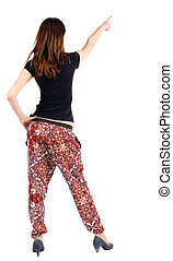 Back view of young brunette woman pointing at wall