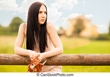 Woman in a Field - beautiful woman standing at a hurdle...