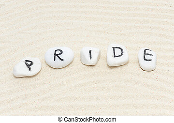 Pride word on group of stones with sand background
